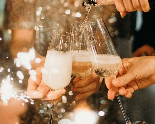 person-pouring-champagne-on-champagne-flutes-3171770